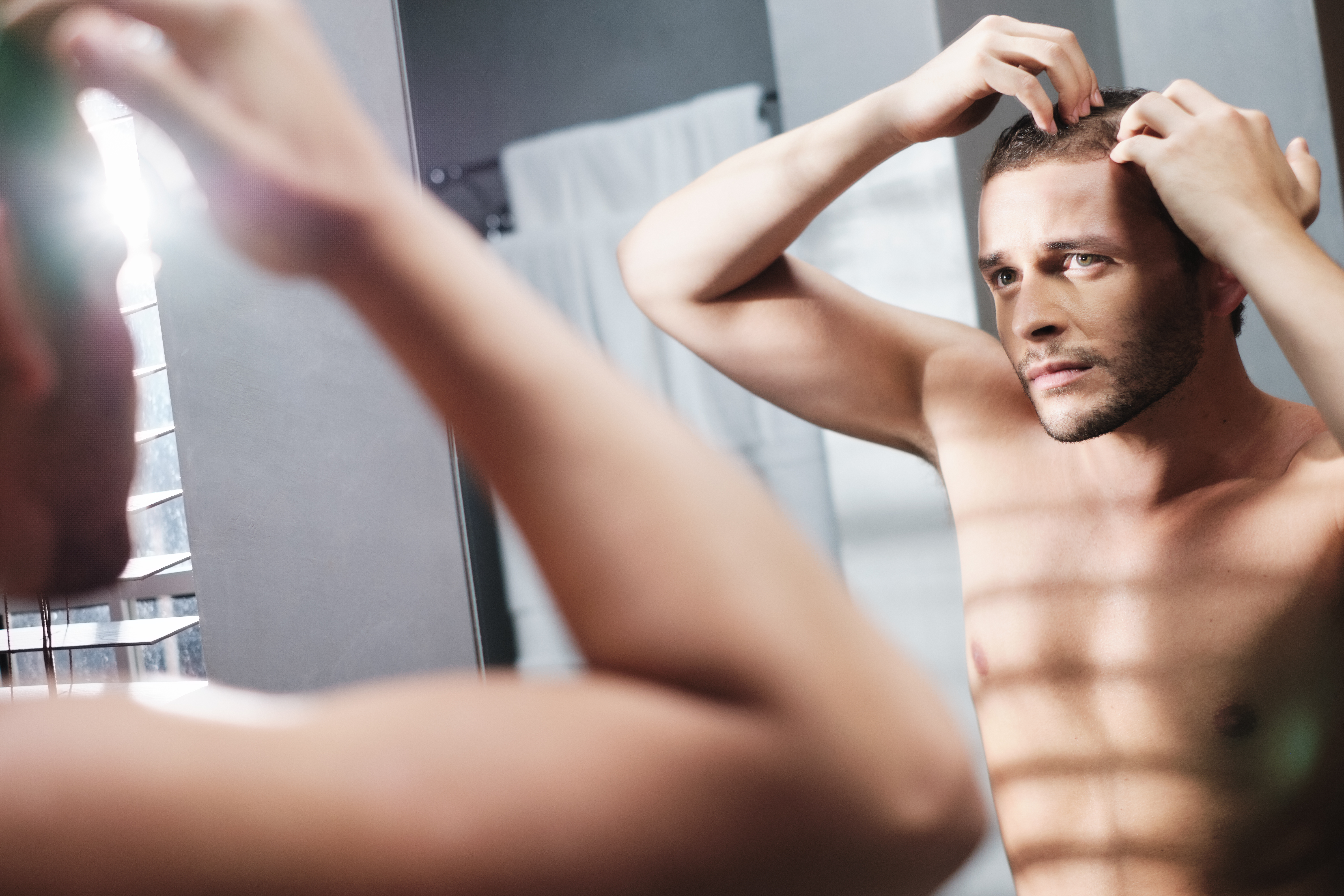 A Concerned man looking in the mirror