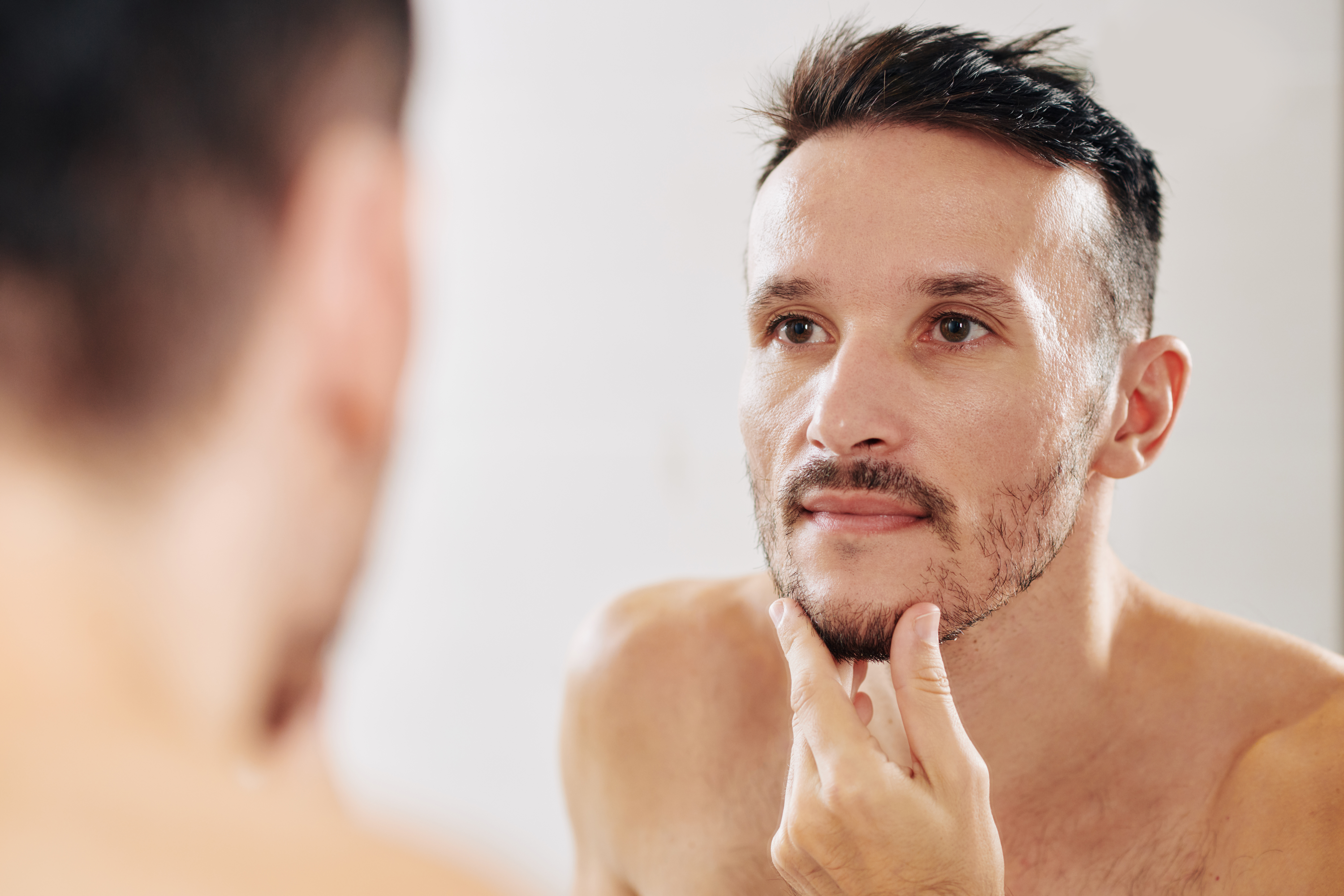 A Handsome Man stokes his refined chin in a mirror